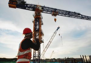 Rigger,Signal,Crane,At,Construction,Site,With,Walkie;talkie